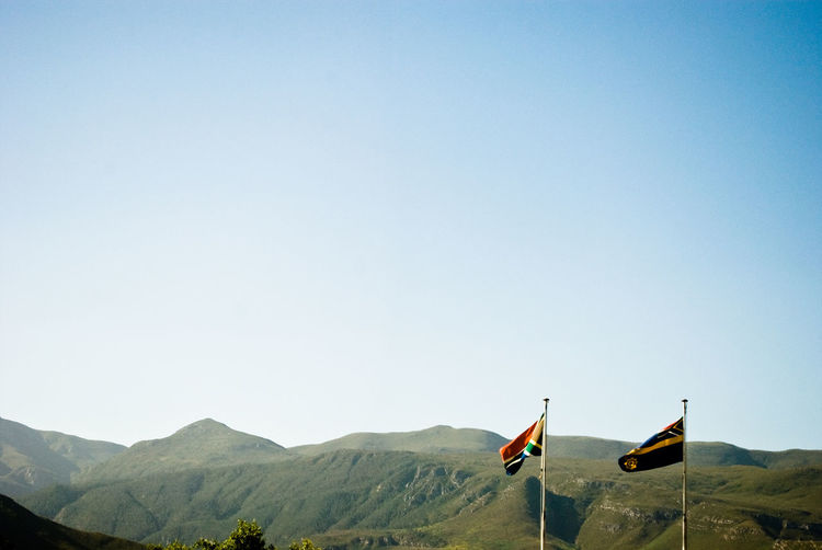 South african flag and mountains against clear sky on sunny day