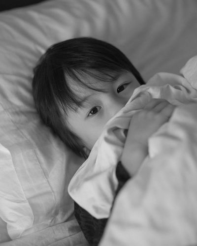 Young kid hides behind the blanket since he does not want his photograph to be taken. Black & White Black And White Childhood Close-up Cute Innocence Kid Leisure Activity Lifestyles Lying Down Resting Shy