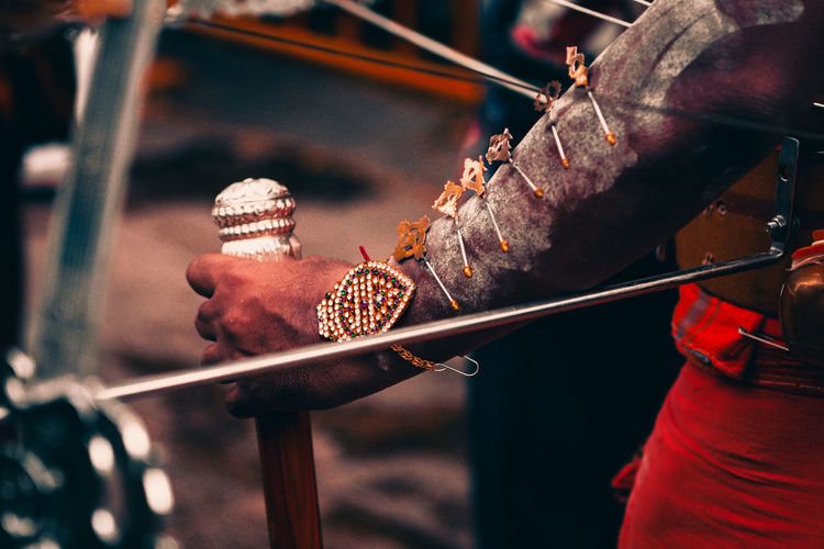 Close-up of a devotee's hand, adorned with vel and holding a walking stick, during thaipusam.