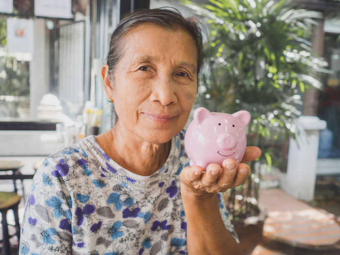 Portrait of smiling woman holding piggy bank