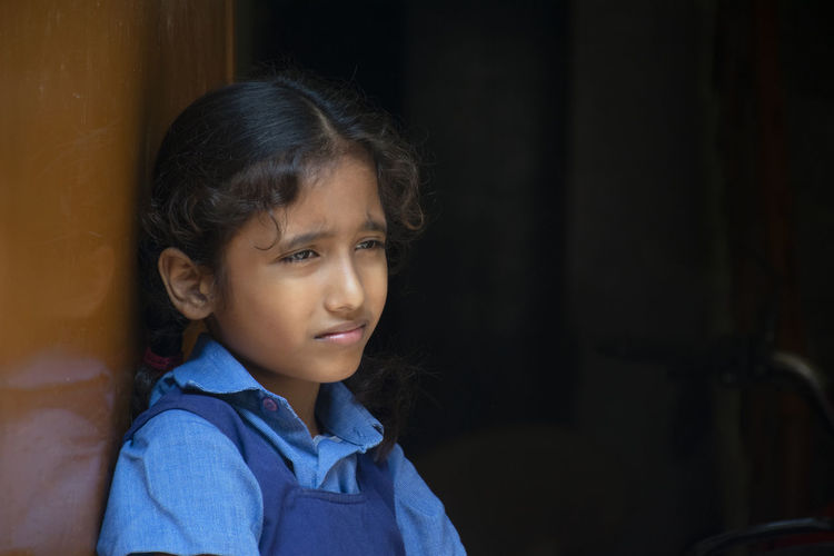 Girl wearing school uniform looking away while standing by wall