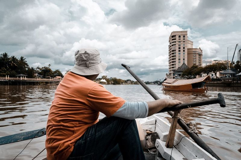 Man holding boat in river against sky