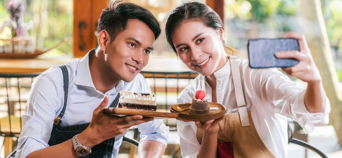 Cheerful couple holding cake while doing selfie