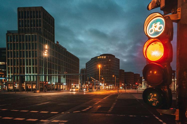 Illuminated city street and buildings against sky