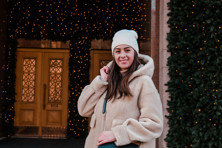 Portrait of smiling woman against christmas decoration during winter