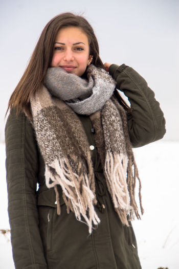 f787cc6cb730a Portrait Of Smiling Young Woman Wearing Warm Clothing Standing In Snow