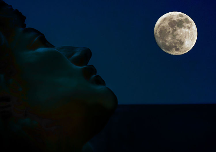 Cropped image of statue against full moon at night