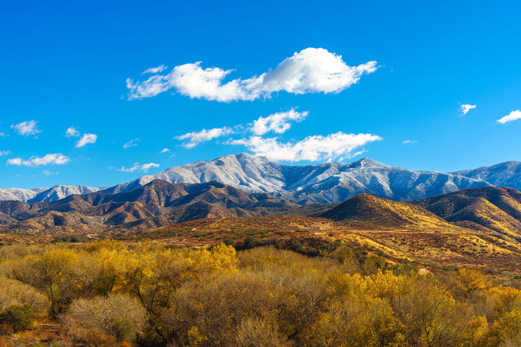 Scenic view of land and mountains against blue sky