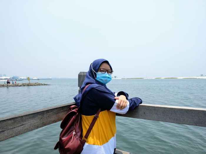 A girl wearing a blue hijab, mask and casual muslim t-shirt standing on the edge of the beach pier