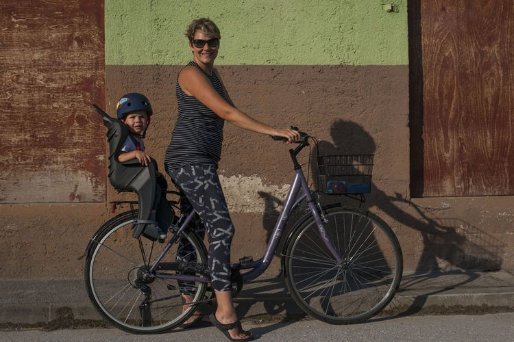 Full length of young couple on bicycle against wall