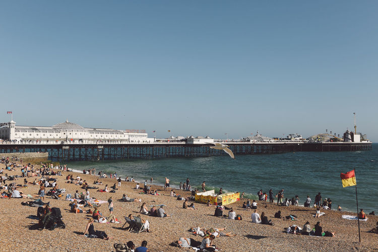 People At Beach By Palace Pier Against Clear Sky