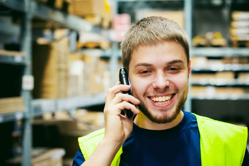 Smiling worker talking on mobile phone in factory