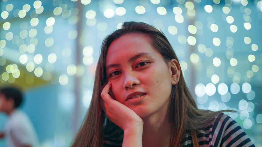 Close-up portrait of young woman against illuminated lights at night