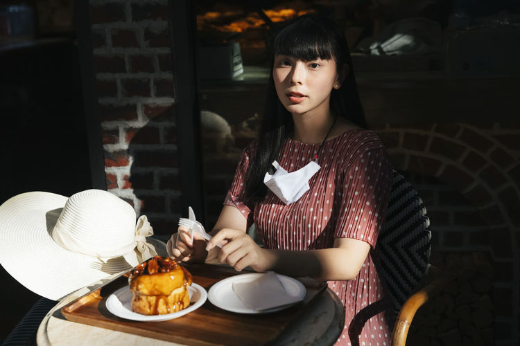 Portrait of young woman sitting at table with food
