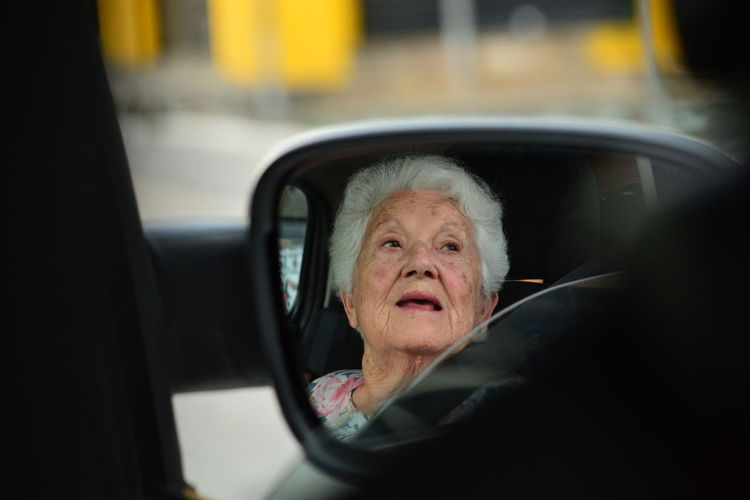 Portrait of old woman in car