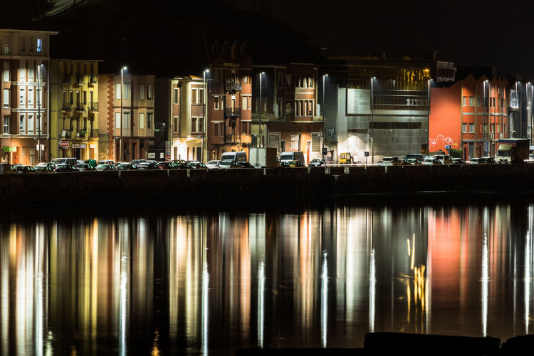 Reflection of illuminated building on water at night