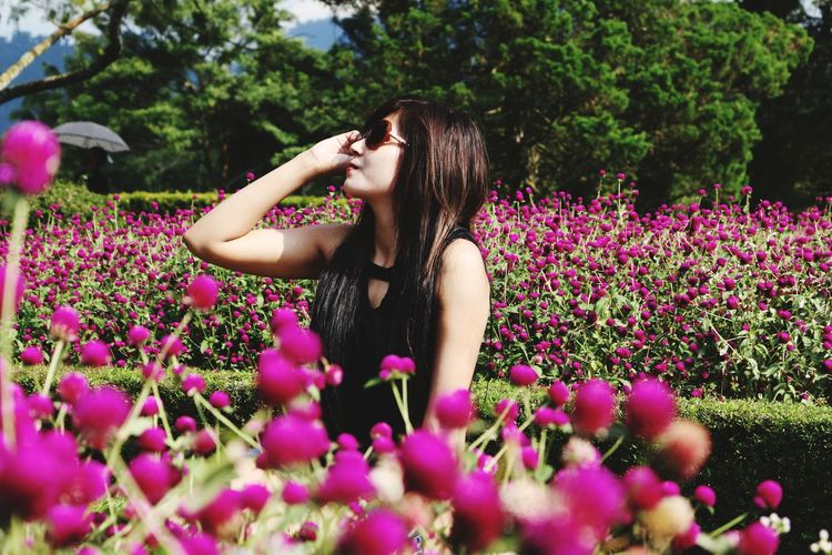 Woman wearing sunglasses while standing amidst pink flowers in garden