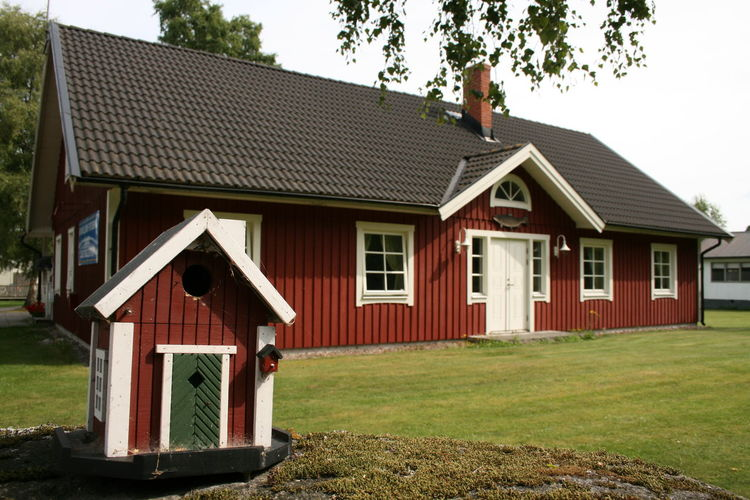 A big house and a tiny (bird) house with an even tinier bird house by the door, all painted in the typical Swedish red colour (faluröd), seen in Grankullavik on the island of Öland, Sweden. Bird House BIG Little Tiny And Giant Tiny House  Tiny Big And Tiny Schwedenhaus Swedish Wooden Houses Wooden House Dreamhome Dreamhouse Real Estate Swedish Lifestyle Grass No People Big And Little Big And Small Red Cottage Swedish Cottage Building House Built Structure Architecture
