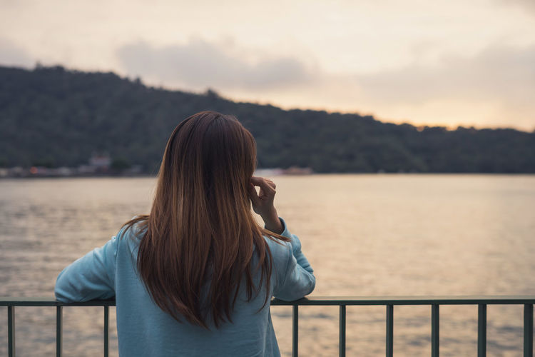 Rear view of woman looking at lake in forest