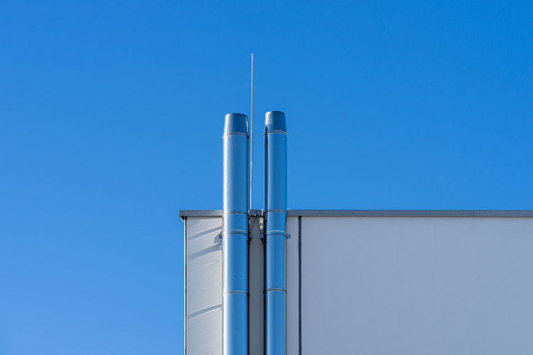 Low angle view of smoke stack against clear blue sky