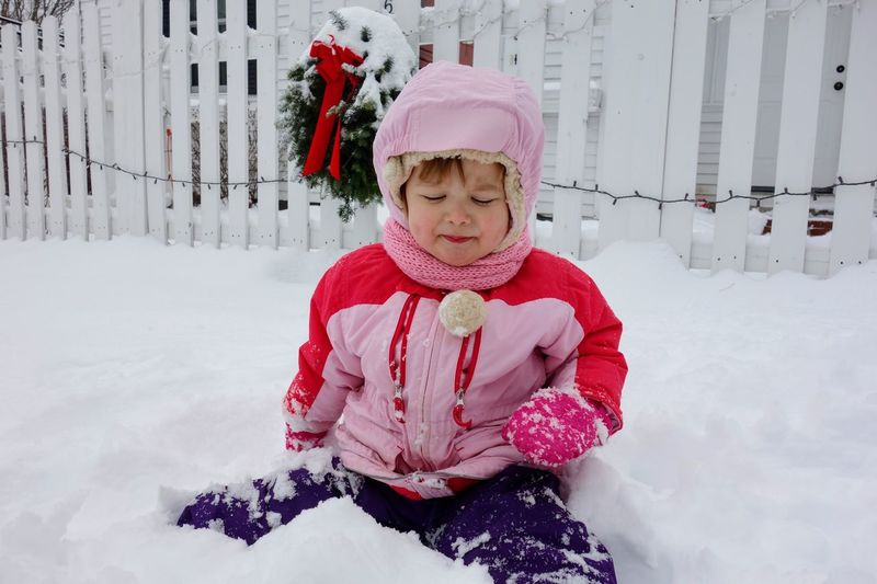 Girl In Warm Clothing Sitting On Snow Covered Field Against Fence