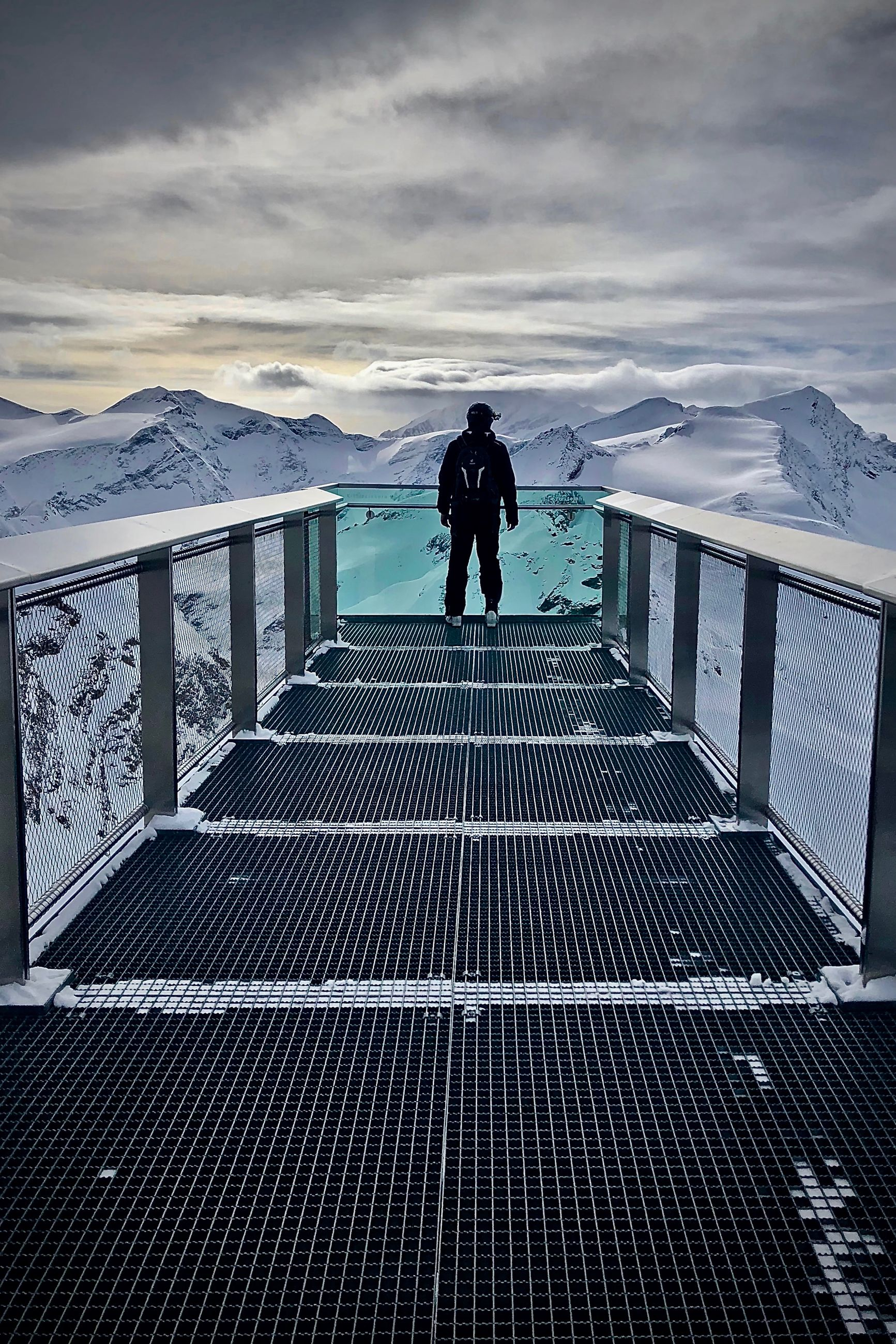 FULL LENGTH OF PERSON STANDING ON RAILING AGAINST MOUNTAIN