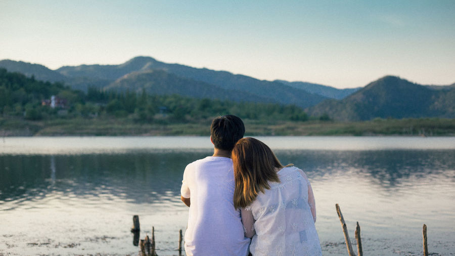 Rear View Of Couple Sitting By Lake Against Mountains
