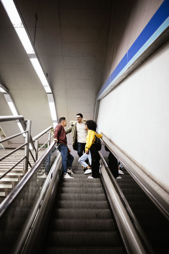 Architecture Indoors  Steps And Staircases Railing Real People Built Structure Men Two People Escalator Convenience Moving Walkway  Transportation Connection Lifestyles Motion Full Length Direction Technology Rear View Ceiling Modern Afrohair Asian  Copy Space Tourist