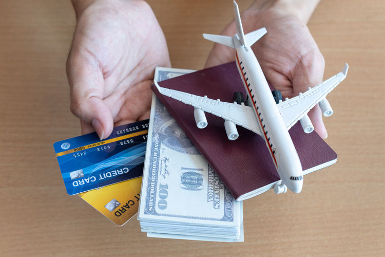 Close-up of hand holding money and passport
