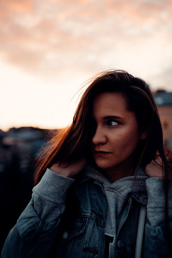 Portrait of beautiful young woman standing against sky during sunset