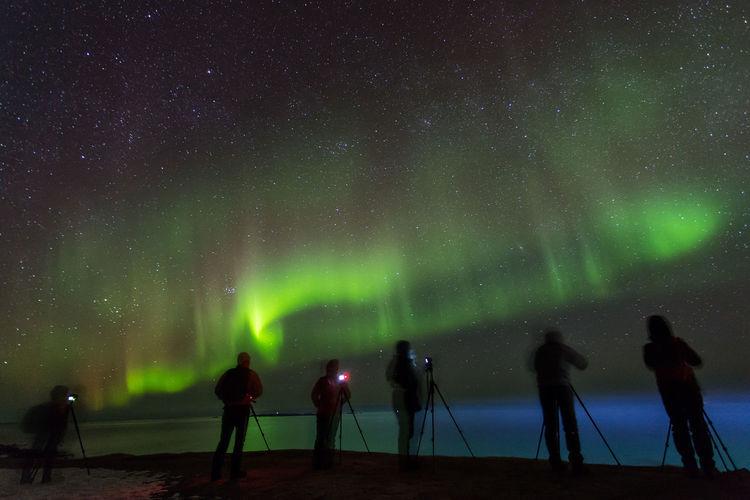 People photographing aurora borealis at night