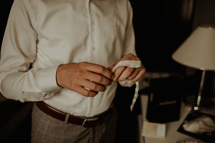 Midsection of man getting dressed while standing at home