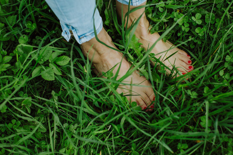 Low section of woman with nail polish standing on grass