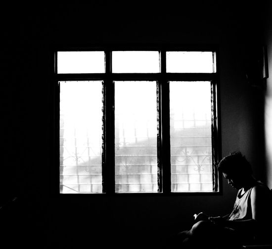 Teenager reading book by window at home