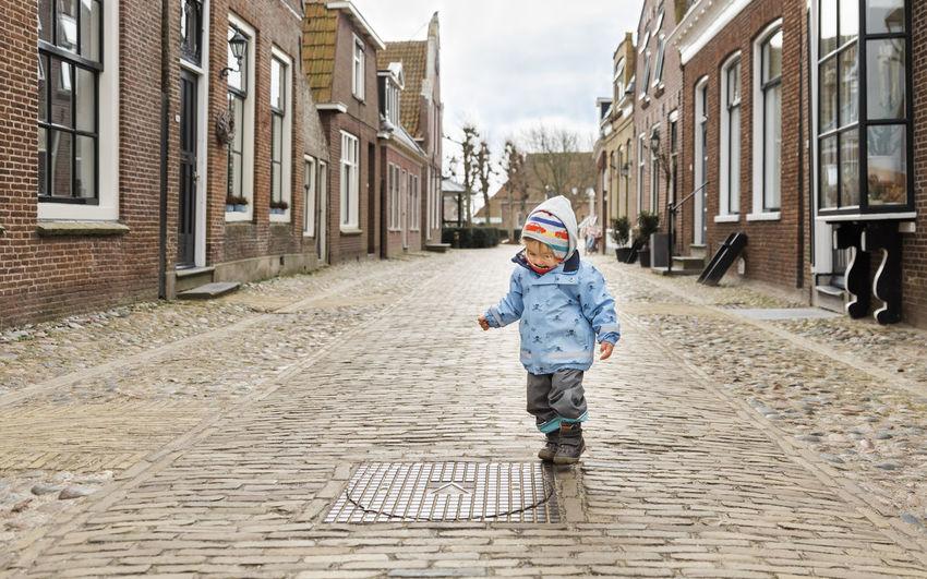 Full length of baby girl walking on footpath amidst buildings