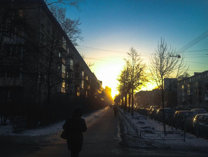 Winter Building Exterior Snow Tree Cold Temperature The Way Forward Outdoors Sky Bare Tree Built Structure Sunset Rear View One Person Architecture Real People Road Nature Day The City Light