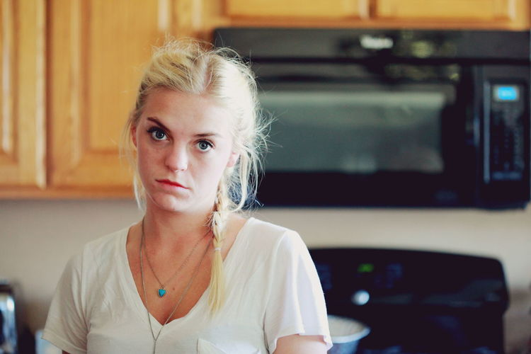 Portrait of young woman standing in kitchen