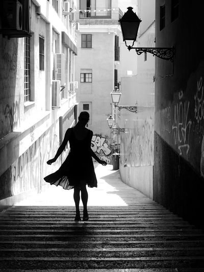 Full length of woman walking on street amidst buildings in city