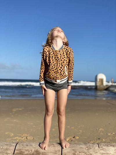 Full length of girl standing at beach against clear sky