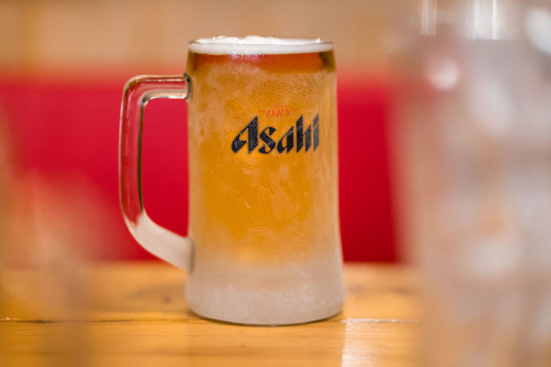 PHUKET, THAILAND - MAR 29, 2019: chilled asahi beer mug with foam on table, asahi is one of favorite japan beer Alcohol Asahi Bar Beer Beverage Brand Brewery Celebrate Chill Cold Company Dinner Drink Foam Frost Glass Gold Illustrative Editorial Japan Label Lager Light Logo Mug Night Party Pour Relax Restaurant Serve Trademark Yellow