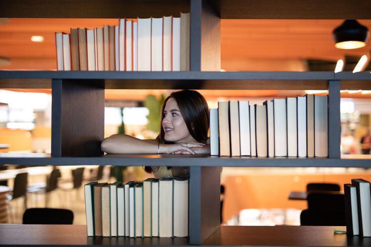 Smiling young woman leaning on bookshelf at library