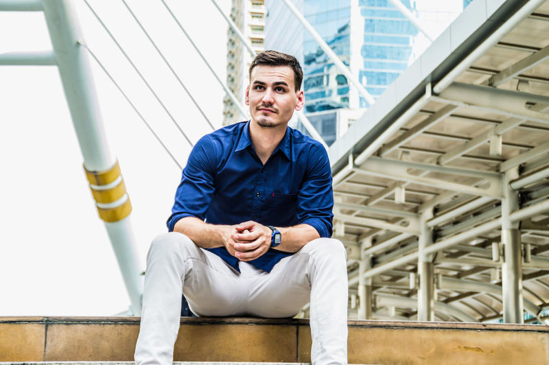 Young businessmen look good on the outside background. Adult Against American Await Background Banner Business Businessman Casual Caucasian Cellular Cheerful City Concrete Confident  Copyspace Education European  Face Fashion Grey Handsome Happy Horizontal Image Intelligent Leaning Man Masculine Outdoor People Photo Portrait Smart Smiling Student Study Style Stylish Success Successful Teach Trend Trendy Using Wait White Work Young Youth