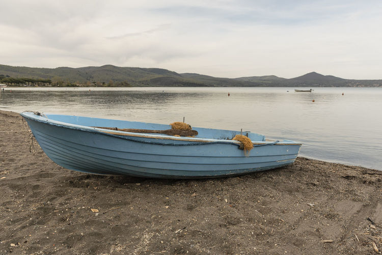 Boats moored on shore by lake against sky