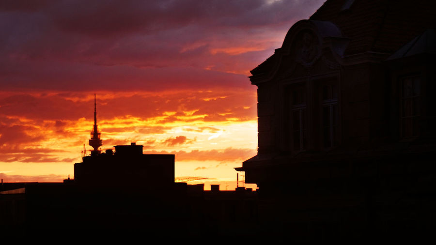 Low angle view of silhouette buildings against dramatic sky