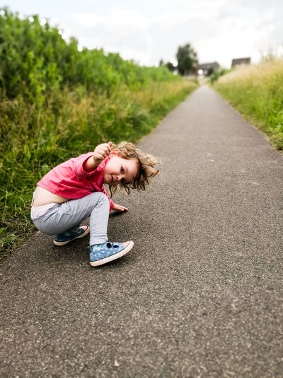 Portrait of cute girl gesturing while crouching on road against sky