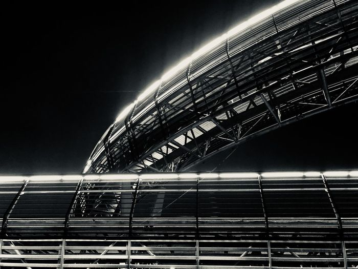 Low angle view of illuminated bridge against clear sky at night