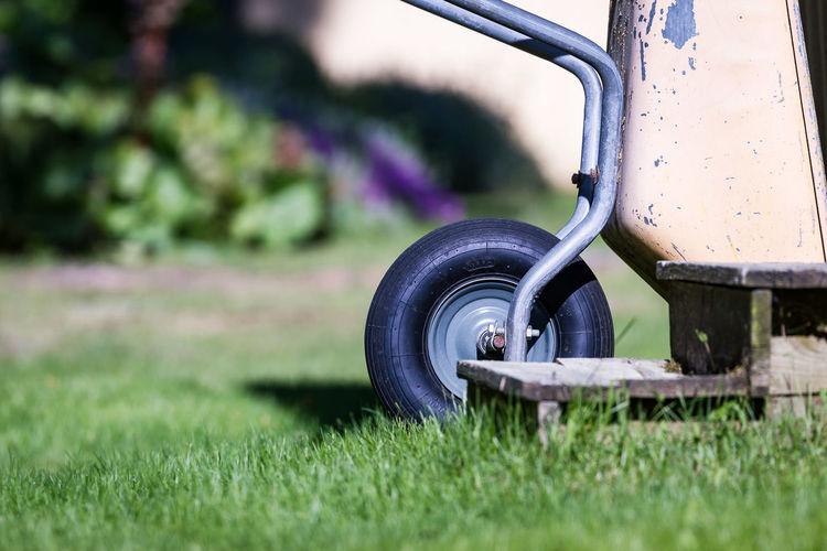 Wheelbarrow on grassy field at garden