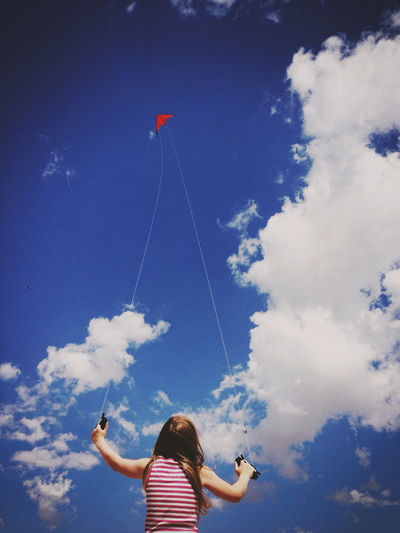 Child flying red kite in blue sky Blue Blue Sky Child Childhood Cloud - Sky Day Flying Girls Headshot Holding Kite Kite - Toy Leisure Activity Lifestyles Low Angle View Nature One Person Outdoors Real People Red Kite Sky Women