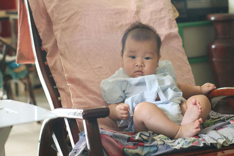 Full length of cute baby girl sitting on sofa