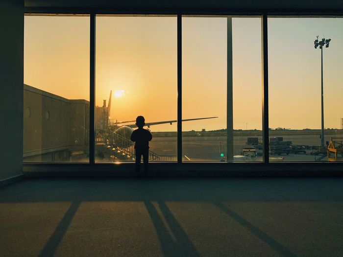 Child standing at airport departure area during sunset